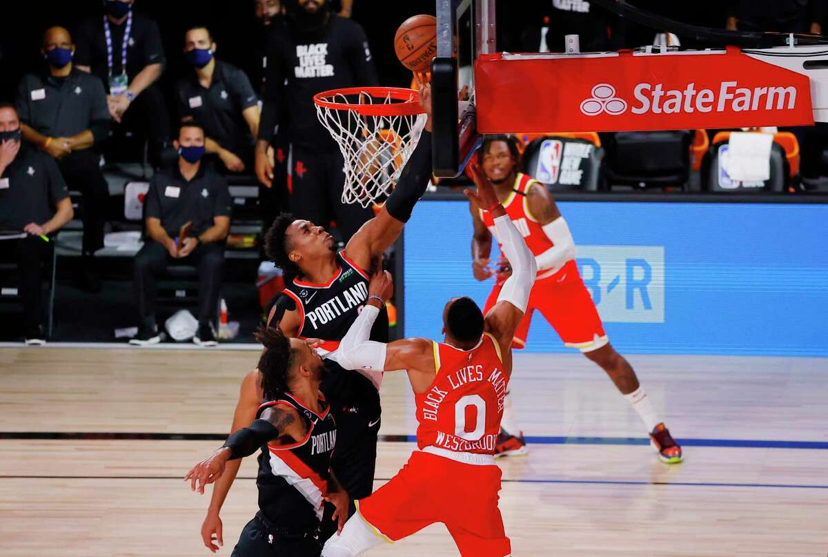 Portland Trail Blazers' Hassan Whiteside (21) blocks a shot by Houston Rockets' Russell Westbrook (0) during the first half of an NBA basketball game Tuesday, Aug. 4, 2020, in Lake Buena Vista, Fla. (Kevin C. Cox/Pool Photo via AP)