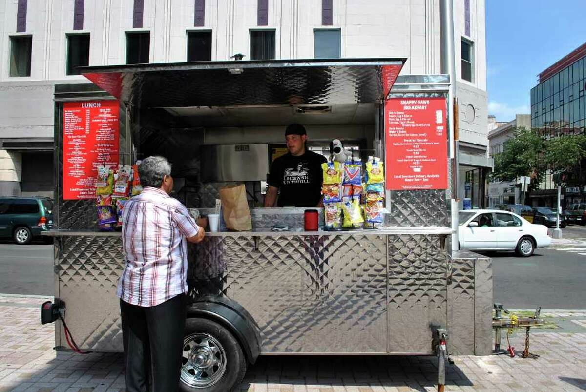 Joe Marzan tends the Snappy Dogs food cart outside the State Courthouse on the corner of Fairfield Avenue and Main Street in Bridgeport. Marzan runs the cart with his mother Janet Marzan.