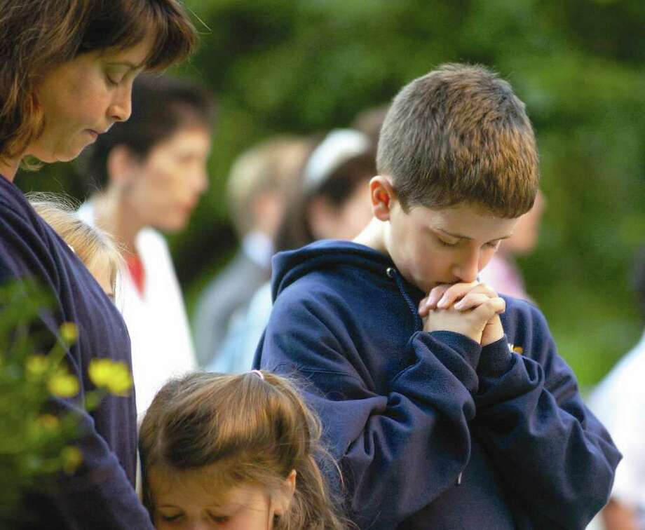 In this 2006 file photo, Hale McSharry, 10, of Riverside, right, prays along with family members during the annual Sept 11. remembrance ceremony at Greenwich Town Hall. Photo: File Photo / Greenwich Time File Photo