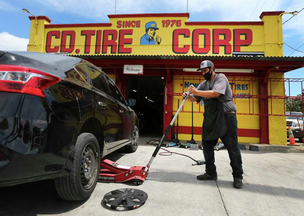 Mike Ruiz lifts up a customer's car to fix a flat on July 22, 2020. CD Tire was started in 1976 by Carlos D. Terrazas on West Commerce at Colorado. The original shop is now owned by his daughter Gabriela Rodriguez and her husband, Enrique Rodriguez. Cousins and other family members own and run the other shops that stretch between Converse and Natalia.