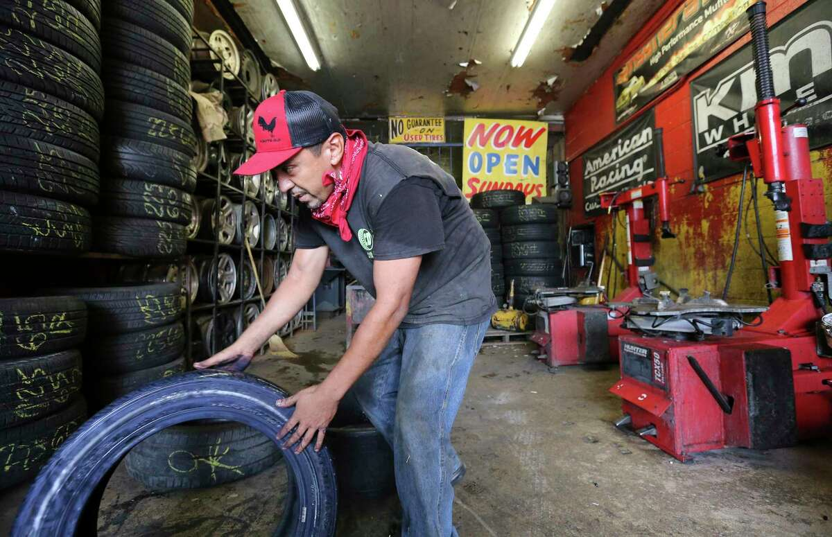 Richard Cervantes cleans up some tires at the original CD Tire shop on West Commerce at Colorado.