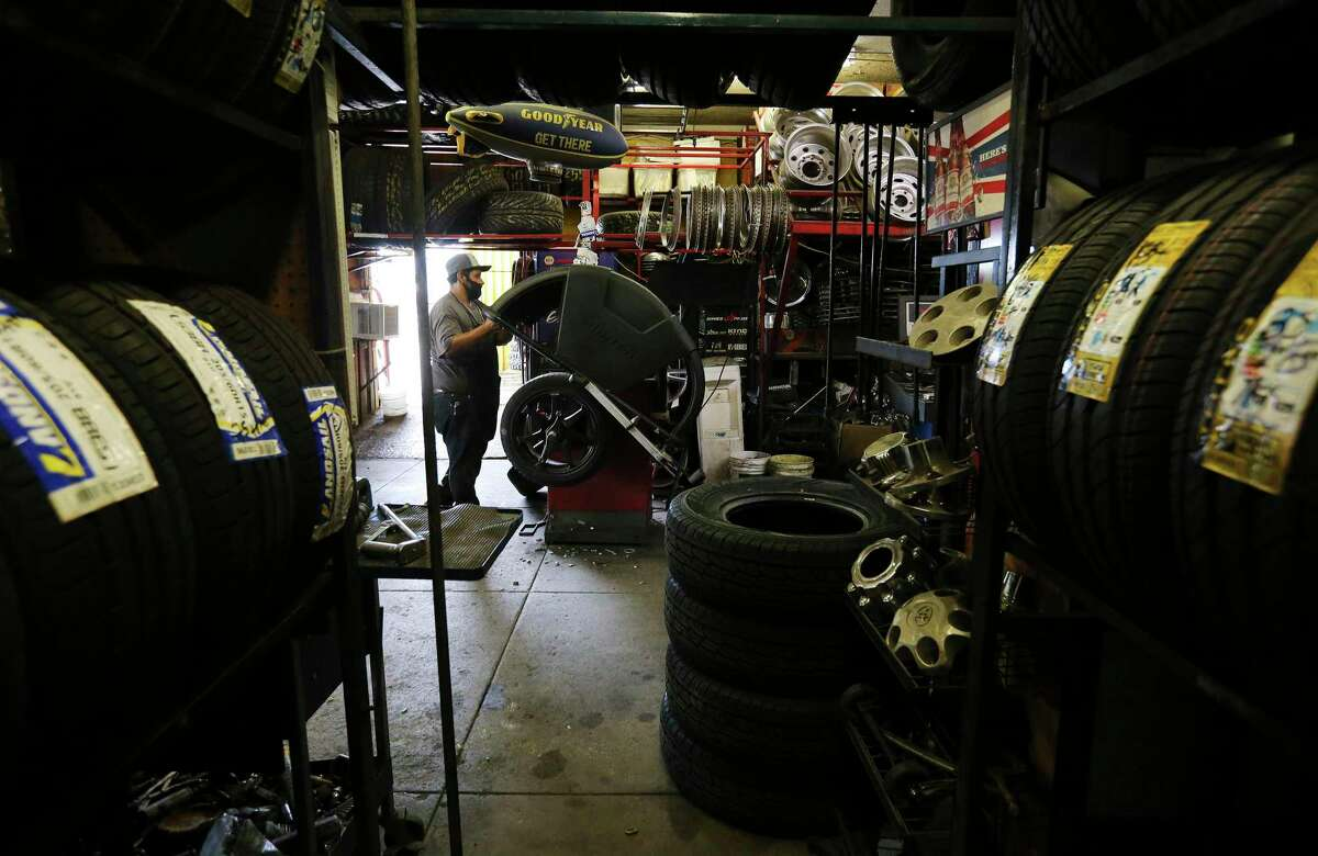 Mike Ruiz balances a tire for a customer at the original CD Tire shop, which opened in 1976.