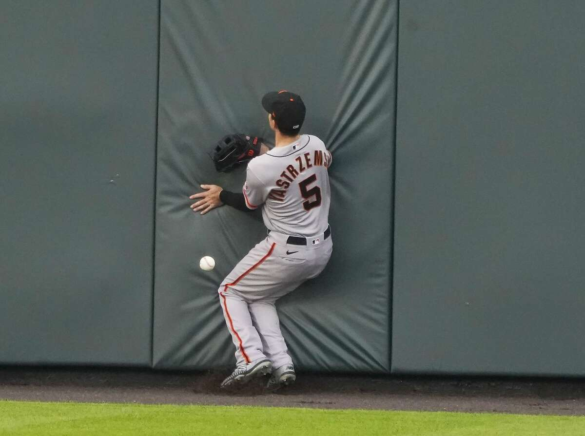 San Francisco Giants right fielder Mike Yastrzemski misses a fly ball at the wall against the Colorado Rockies during the first inning of a baseball game, Tuesday, Aug. 4, 2020, in Denver. (AP Photo/Jack Dempsey)