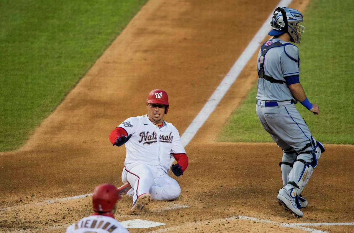 Washington Nationals Asdrubal Cabrera slides to home to score during the third inning of a baseball game against the New York Mets in Washington, Tuesday, Aug. 4, 2020. On the right is Mets catcher TomA!s Nido (3). (AP Photo/Manuel Balce Ceneta)