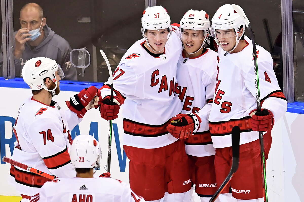 Carolina Hurricanes' Teuvo Teravainen, second from right, celebrates his goal against the New York Rangers with, from left, Jaccob Slavin, Sebastian Aho, Andrei Svechnikov and Haydn Fleury during the second period of an NHL hockey playoff game Tuesday, Aug. 4, 2020, in Toronto. (Frank Gunn/The Canadian Press via AP)