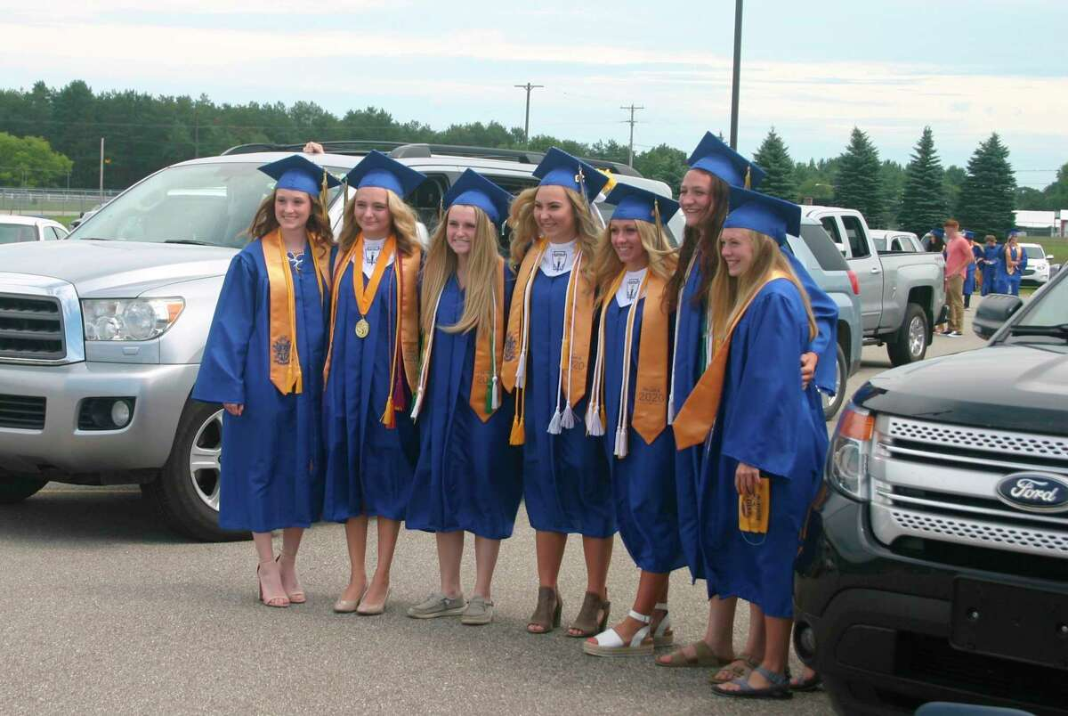Evart High School senior girls gather for a photo as they prepare for the graduation ceremony on Aug. 1.