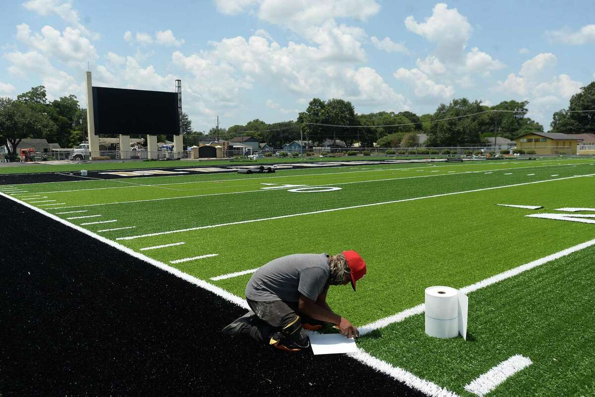 A worker finishes trimming on the new turf as renovation work continues at Nederland High School's stadium Tuesday. The turf field has been laid, and trim work continues, as well as upgrades to the scoreboard. Photo taken Tuesday, August 4, 2020 Kim Brent/The Enterprise