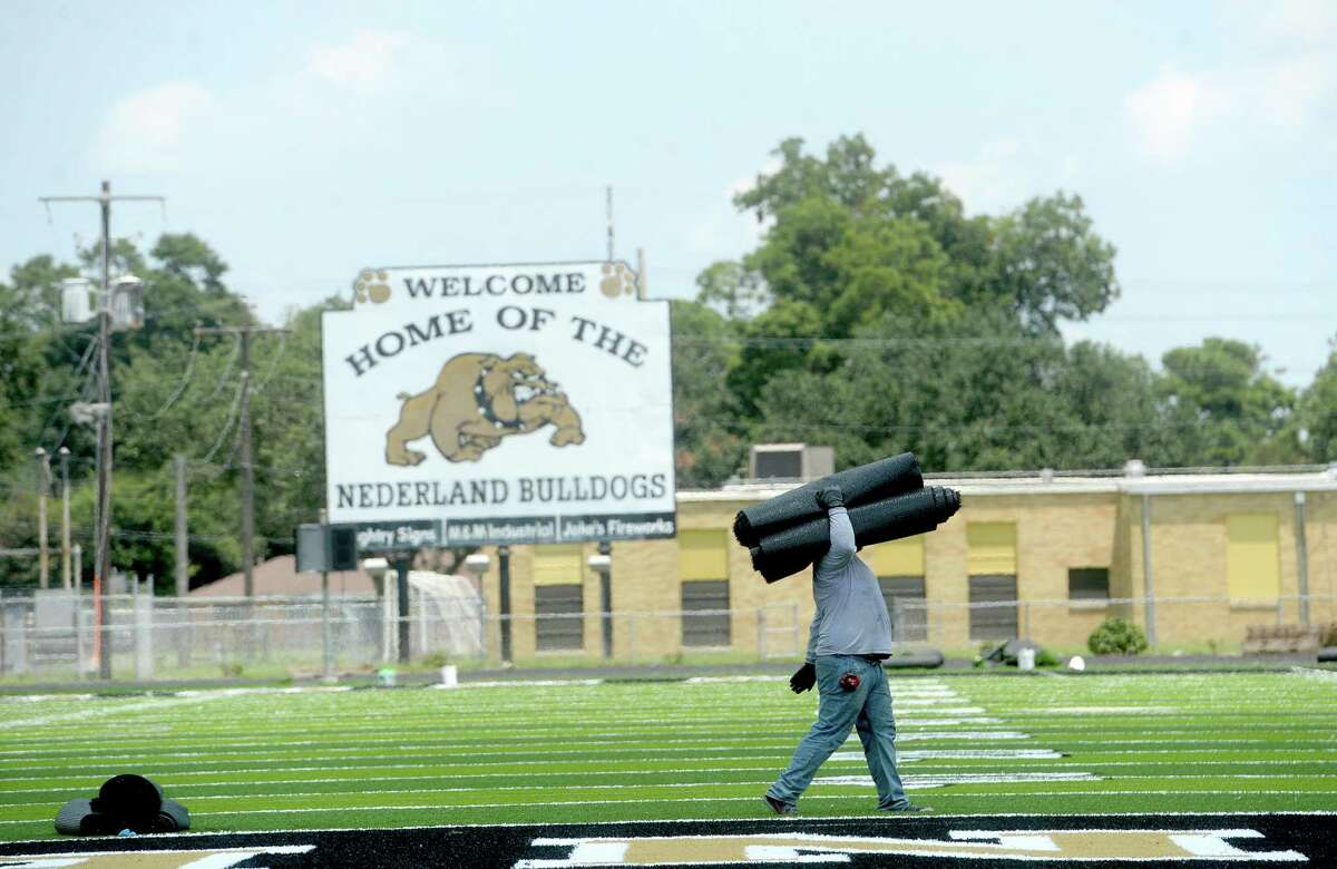 A worker carries rolls of turf across the western end zone as renovation work continues at Nederland High School's stadium Tuesday. The turf field has been laid, and trim work continues, as well as upgrades to the scoreboard. Photo taken Tuesday, August 4, 2020 Kim Brent/The Enterprise