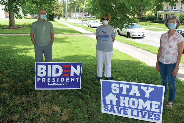 Dennis Ptak (from left), Morgan County Democrats President Judith Luckenbach Nelson and Jeannie Zeck stand with yard signs supporting Democratic presidential presumptive nominee Joe Biden and staying home during the COVID-19 pandemic. The three worry that thefts of yard signs are becoming an issue.