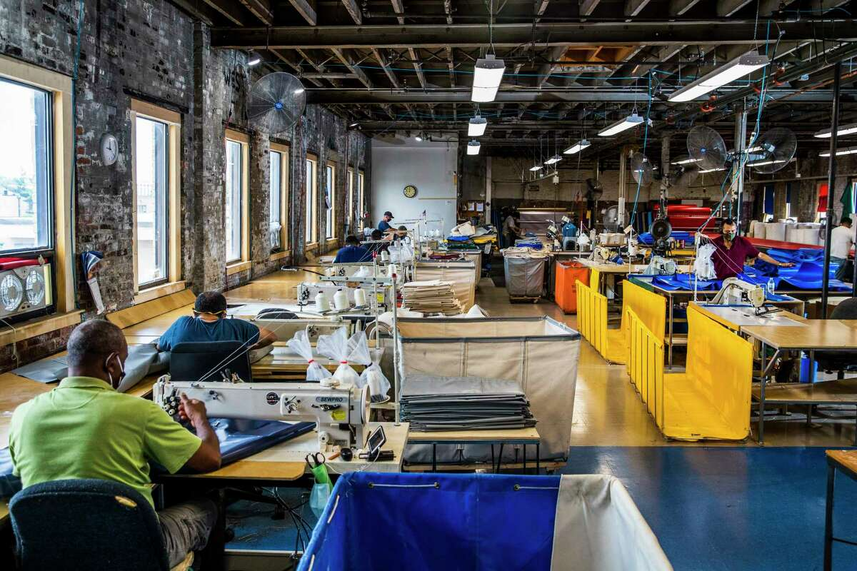 Workers process materials in the Steele Canvas factory in Chelsea, Mass.