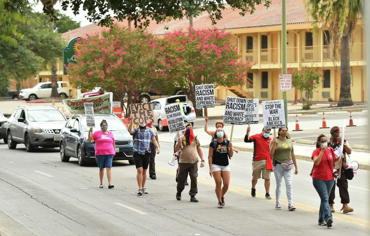 Rachel Tucker leads marchers and a caravan near public safety headquarters during a National Day of Protest against evictions, foreclosures, police brutality and racism Saturday in downtown San Antonio.