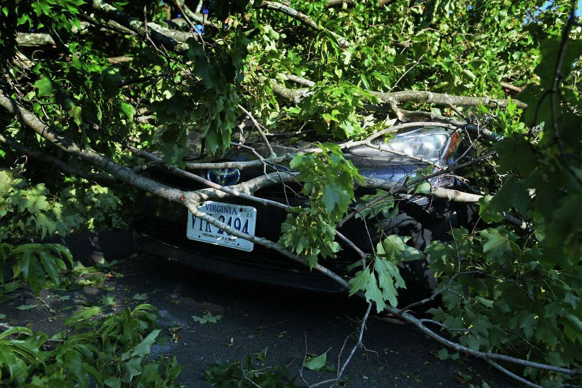 A car is buried under a tree limb near Williams Street in damage wrought by tropical storm Isaias on Wednesday in Norwalk.