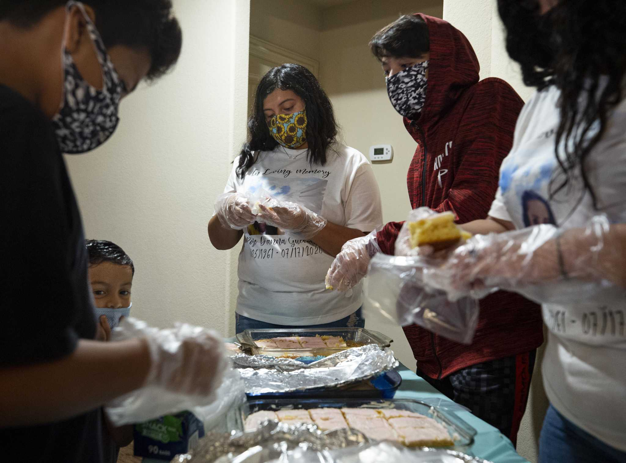 Family members work to put together food orders during a Aug. 1 benefit in Houston for Rosie Guevara, who died of COVID-19 at 59.