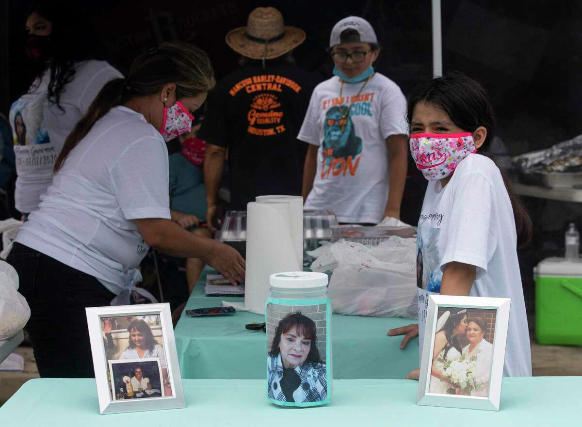 Photographs of Rosie Guevara, who died of COVID-19, and a donation jar on a table at a Houston benefit Aug. 1 to raise money for her cremation.