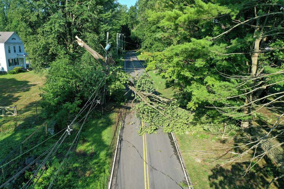 A tree hangs on power lines in New Canaan Wednesday in the aftermath of Tropical Storm Isaias. Photo: Patrick Sikes / For Hearst Connecticut Media