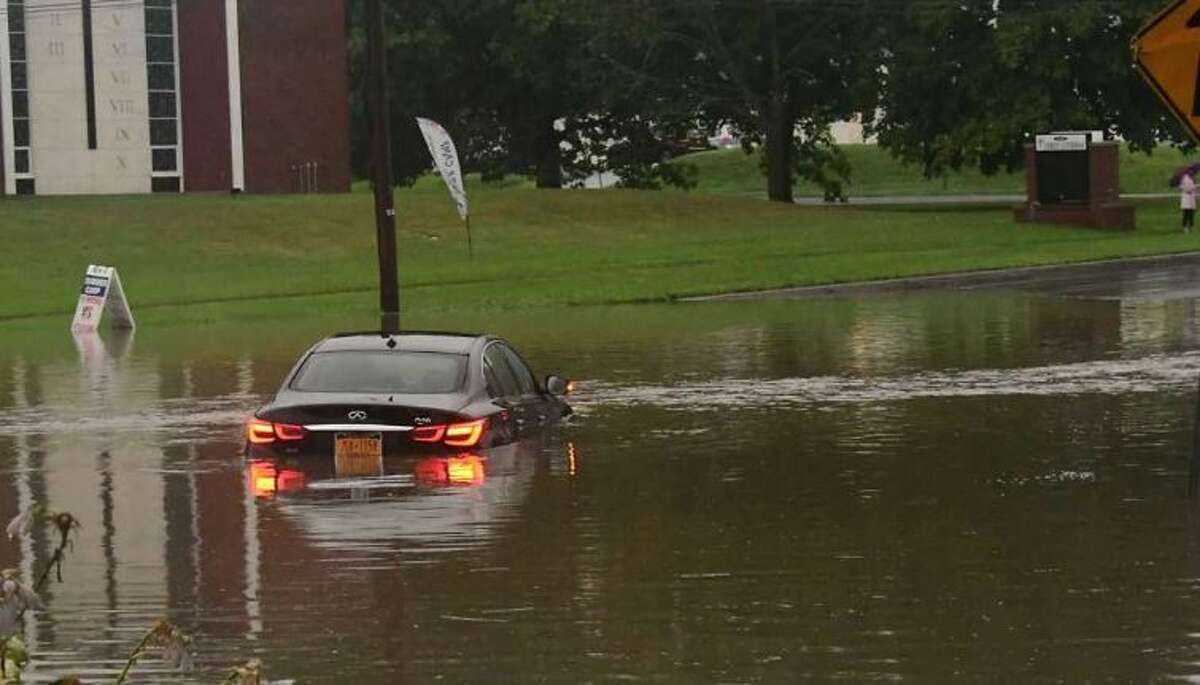 A car is seen stuck stuck in water in front of Stuyvesant Plaza on Rt. 20 which often floods with heavy rain on Tuesday, Aug. 4, 2020 in Guilderland, N.Y. Heavy rains due to Tropical Storm Isaias brought flooding to the area.