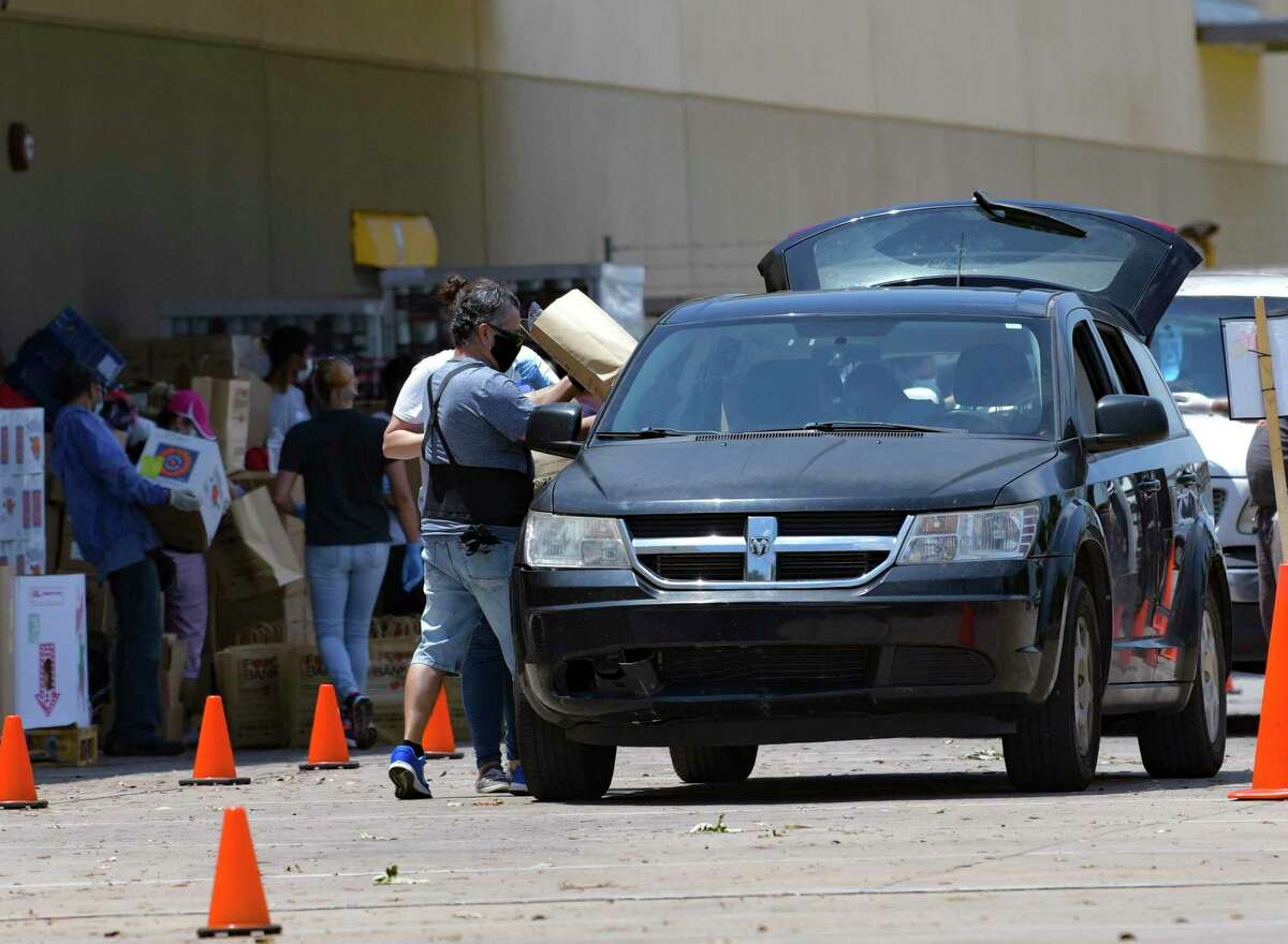 Workers at the San Antonio Food Bank load cars during a distribution Tuesday. Such distributions have been a hallmark of the pandemic, but the city's workforce development program has the potential to reshape our economic recovery.