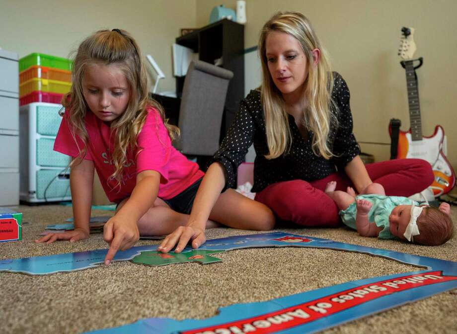 Cashlee Hopkins, 8, and her mother, Melody O'Dell, work on a puzzle inside her playroom July 31 in Houston. O'Dell said Cashlee struggled with the isolation brought on by the novel coronavirus pandemic this summer, prompting her to choose in-person classes for Cashlee once schools in Humble ISD reopen. Photo: Godofredo A. Vásquez, Houston Chronicle / Staff Photographer / © 2020 Houston Chronicle