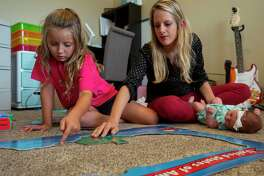 Cashlee Hopkins, 8, and her mother, Melody O'Dell, work on a puzzle inside her playroom July 31 in Houston. O'Dell said Cashlee struggled with the isolation brought on by the novel coronavirus pandemic this summer, prompting her to choose in-person classes for Cashlee once schools in Humble ISD reopen.