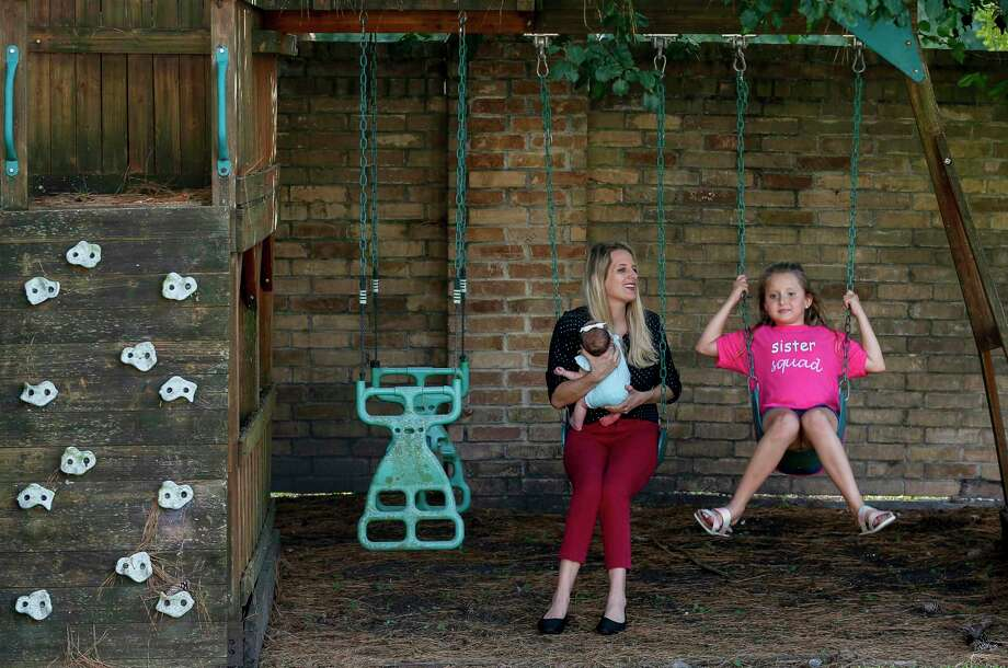 Melody O'Dell carries her one-month-old daughter Mackenzie as her eight-year-old daughter Cashlee plays on the swing in their backyard Friday, July 31, 2020, in Houston. Melody and Cody have elected to send Cashlee back to Summerwood Elementary School in Humble ISD once the districts resumes in-person classes. Photo: Godofredo A. Vásquez, Houston Chronicle / Staff Photographer / © 2020 Houston Chronicle