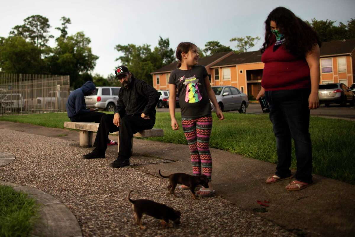 The Partida family enjoys the evening together on the courtyard of their apartment complex on Aug. 1 in Houston. The family of five lives in a densely populated section of northern Harris County, which increases their level of concern that COVID-19 could spread easily if schools reopen this fall.