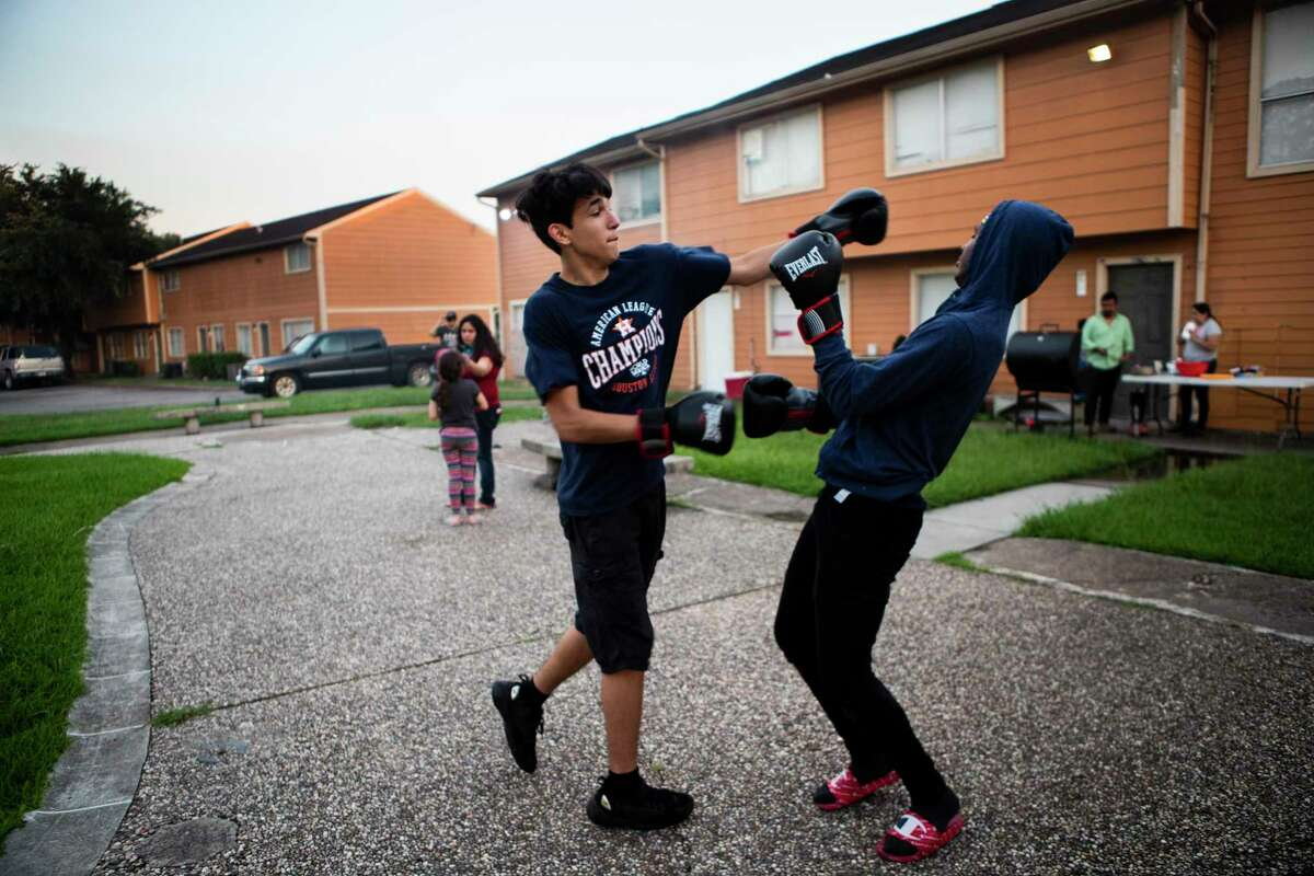 Dominic Partida, center, 15, and his godbrother Jalen Parsons, right, 17, practice boxing on the courtyard of their apartment complex on Aug. 1 in Houston. The mothers and fathers of Dominic and Jalen worry about the health impact of COVID-19 on students in schools, prompting them to choose virtual-only classes to start the year.