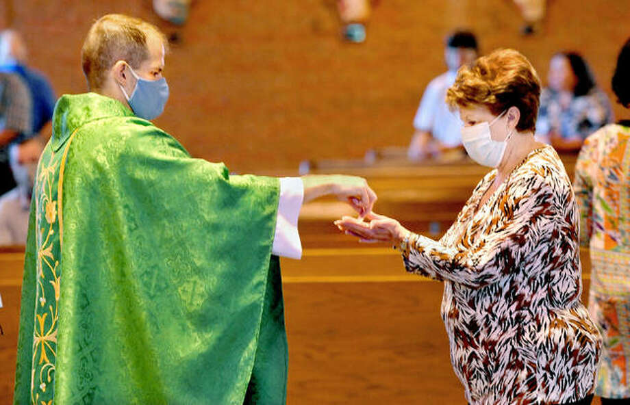 Father Rob Johnson, left, gives communion to Gloria Fuhrhop of Collinsville during mass Sunday at Mother of Perpetual Hope Catholic Church in Maryville. Mask wearing is required due to the COVID-19 pandemic. Photo: Thomas Turney | For The Intelligencer
