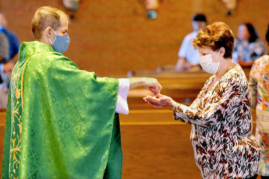 Father Rob Johnson, left, gives communion to Gloria Fuhrhop of Collinsville during mass Sunday at Mother of Perpetual Hope Catholic Church in Maryville. Mask wearing is required due to the COVID-19 pandemic.