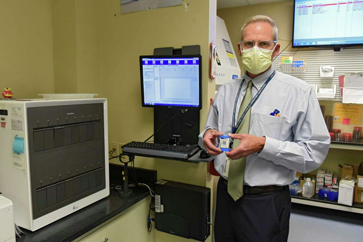 Richard Vandell, administrative director, Laboratory Services, holds a sample cartridge which is put in the GeneXpert machine, at left, in the Saratoga Hospital laboratory where COVID-19 tests are performed on Wednesday, Aug. 5, 2020 in Saratoga Springs, N.Y (Lori Van Buren/Times Union)