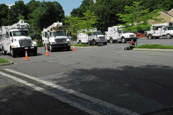 Crews with utility trucks down from Brunswick, Canada, await their orders Wednesday at Carluzzi's Georgetown Market. Eversource brought in crews from outside Connecticut to help restore power.