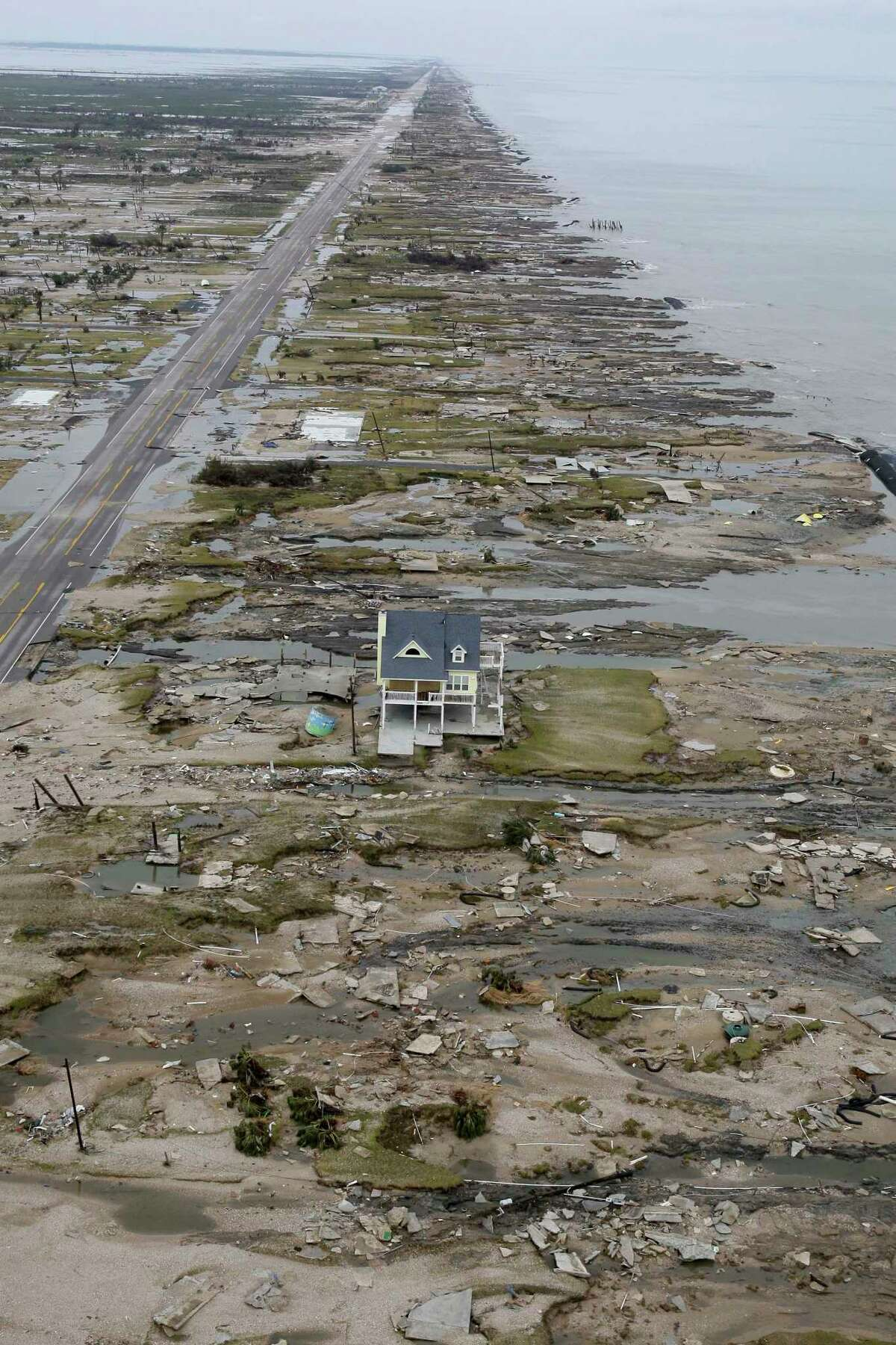 With the Gulf of Mexico seen at right, a beachfront home stands among the debris in Gilchrist, Texas on Sunday, Sept. 14, 2008 after Hurricane Ike hit the area. Ike was the first major storm to directly hit a major U.S. metro area since Hurricane Katrina devastated New Orleans in 2005. (AP Photo/David J. Phillip, Pool)