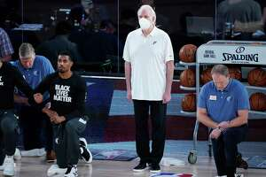 San Antonio Spurs head coach Gregg Popovich stands beside his players as they kneel before an NBA basketball game against the Memphis Grizzlies, Sunday, Aug. 2, 2020, in Lake Buena Vista, Fla. (AP Photo/Ashley Landis, Pool)