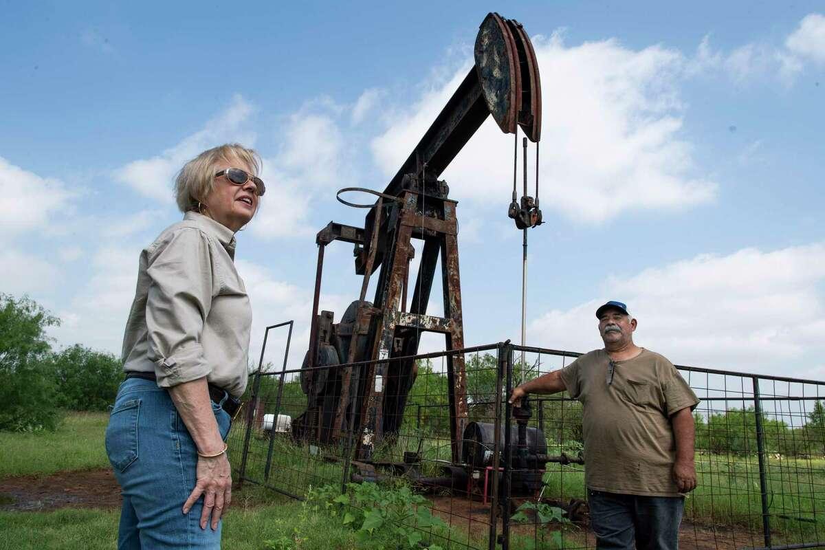 Marsha Hendler, founder and CEO of TerraFina Energy LLC, checks on a company pump jack with employee David Martinez.