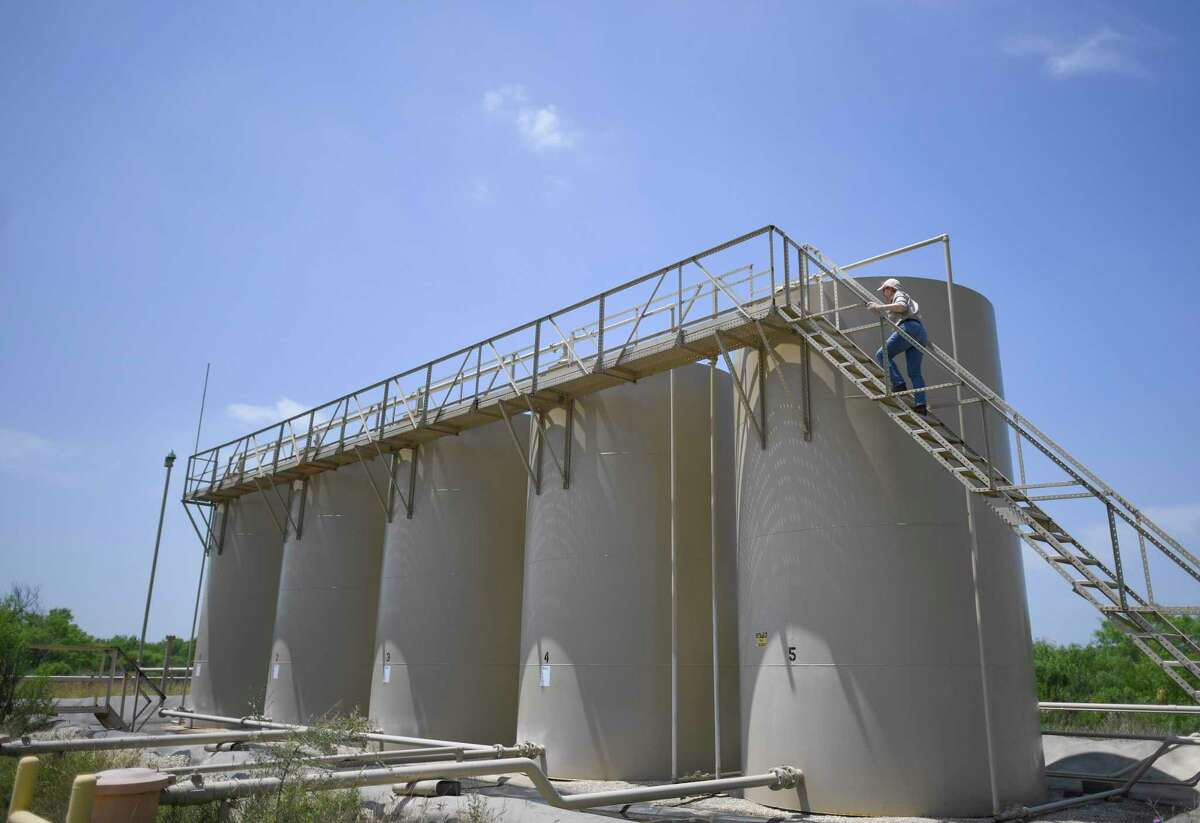 Hendler climbs to the top of a group of five 400-barrel capacity oil tanks in Zavala County. Hendler went from the hospitality industry to marketing to the oil and gas industry.