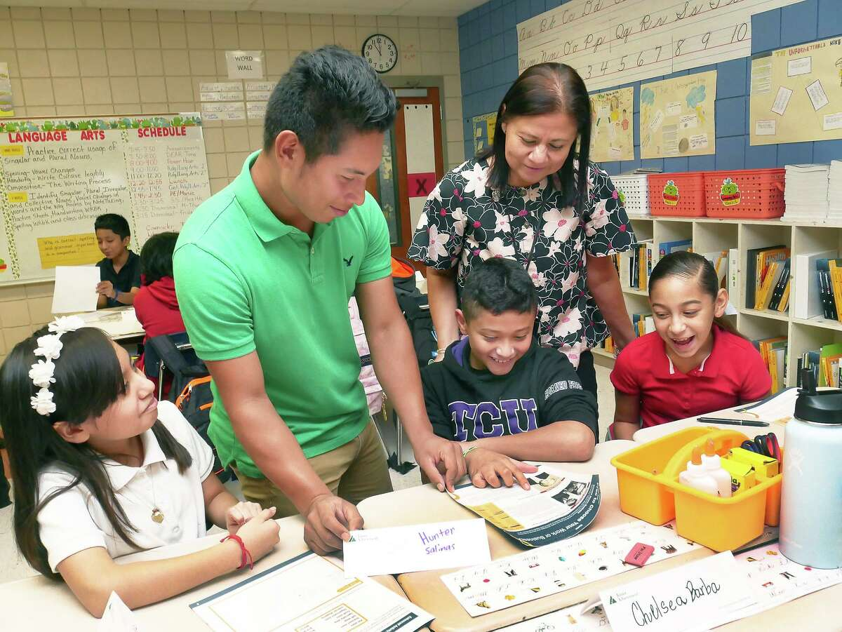 C.L. Milton Elementary fifth grade teacher Maria del Carmen Gammon looks on as her students America Hernandez, Ethan Hunter Salinas and Leila Ramirez work on a lesson with Nixon High School student Oscar Montes who visited the class as part of the Junior Achievement Program.