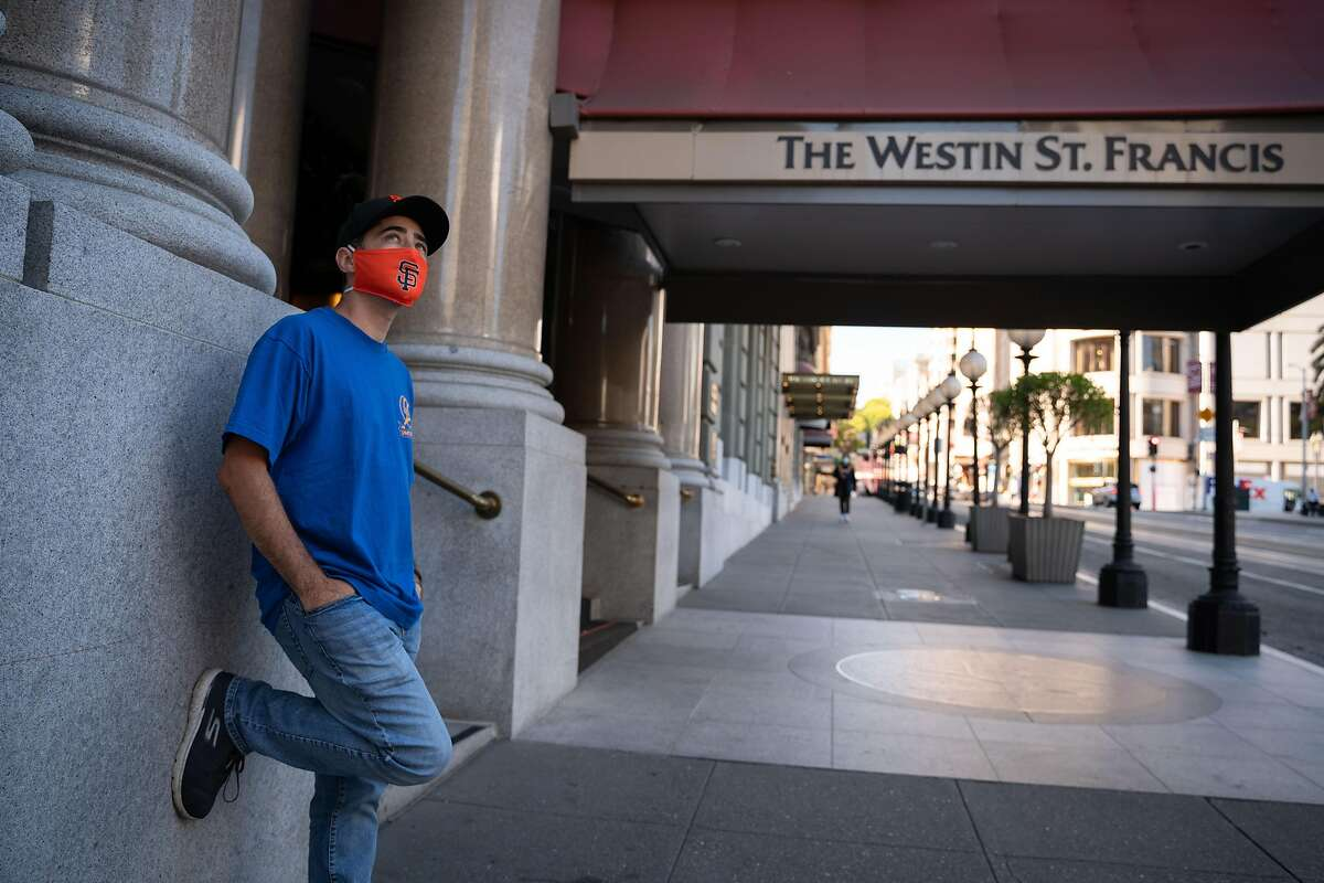 """Nicholas Javier, 39, of San Francisco, poses for a photo outside of the Westin St. Francis Hotel in San Francisco, Calif., on Monday, August 3, 2020. Javier moved in with his partner after being laid off from his job as a server at the hotel due to the coronavirus pandemic. """"I'm one of the lucky ones,"""" said Javier. """"I have someone to help me through this. Some people don't have that."""""""