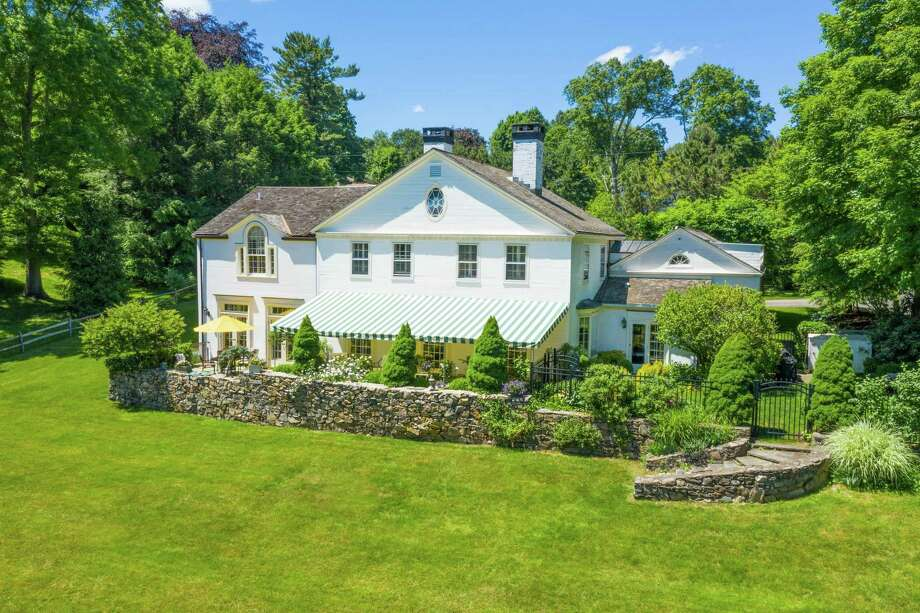 This elegant yet comfortable property features a long bluestone patio covered with an awning and attractive landscaping.