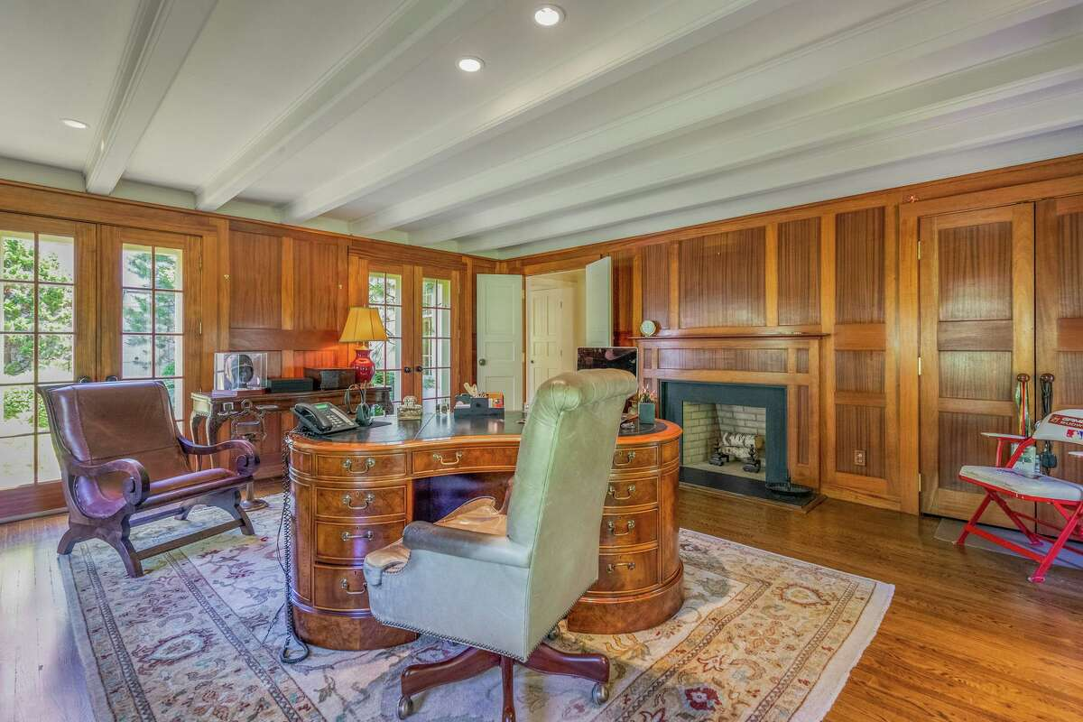 The office features a fireplace, paneled walls and a beamed ceiling, and two sets of multi-paned French doors to the attractive grounds.