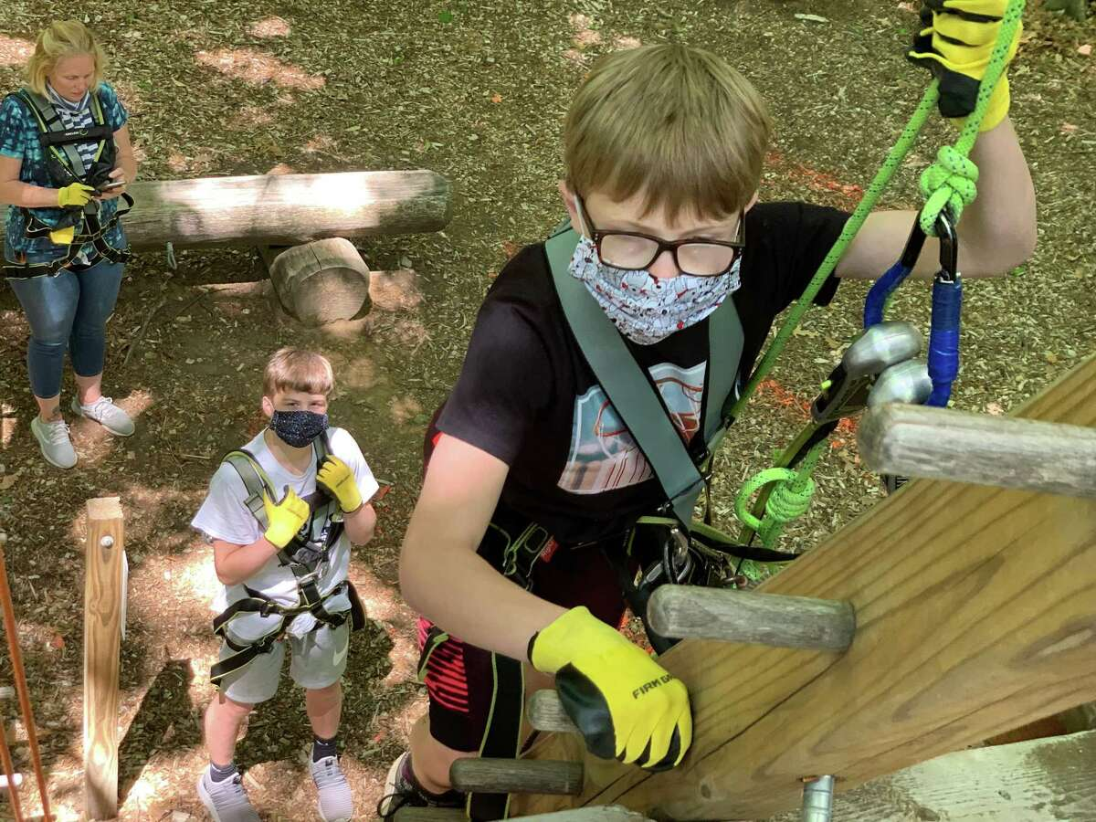 A family experiences the ropes course atNomad's Outdoor Adventure in South Windsor.