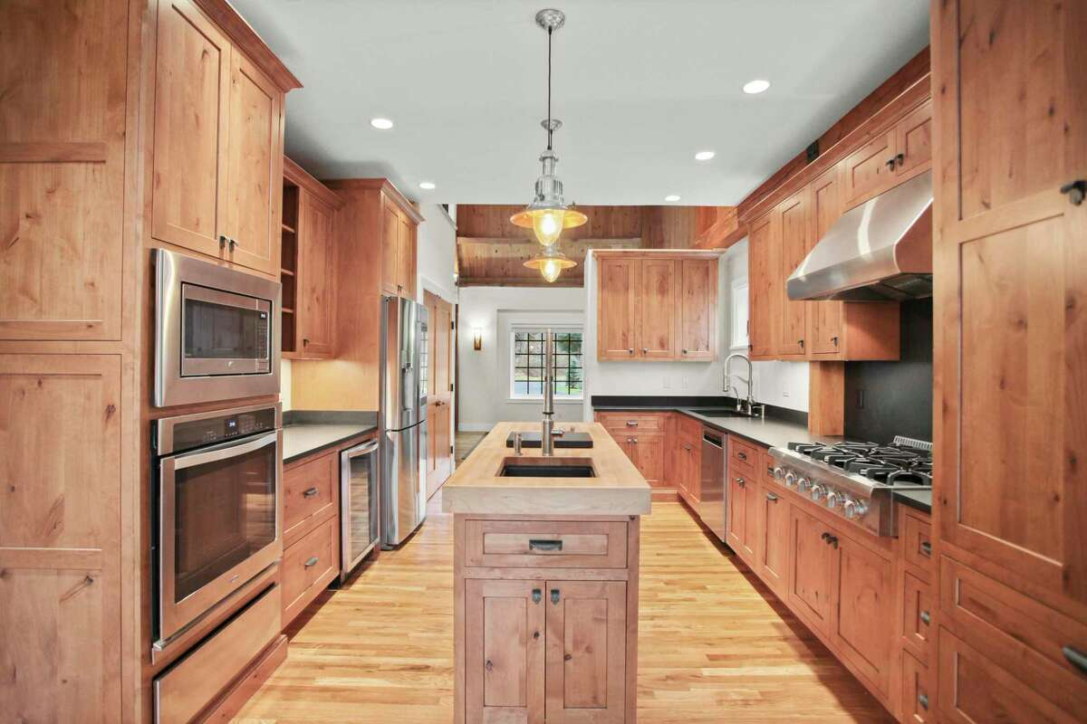 In the gourmet eat-in kitchen there is a center island topped with a thick butcher's block counter, custom cabinetry, honed granite counters, and a pantry.