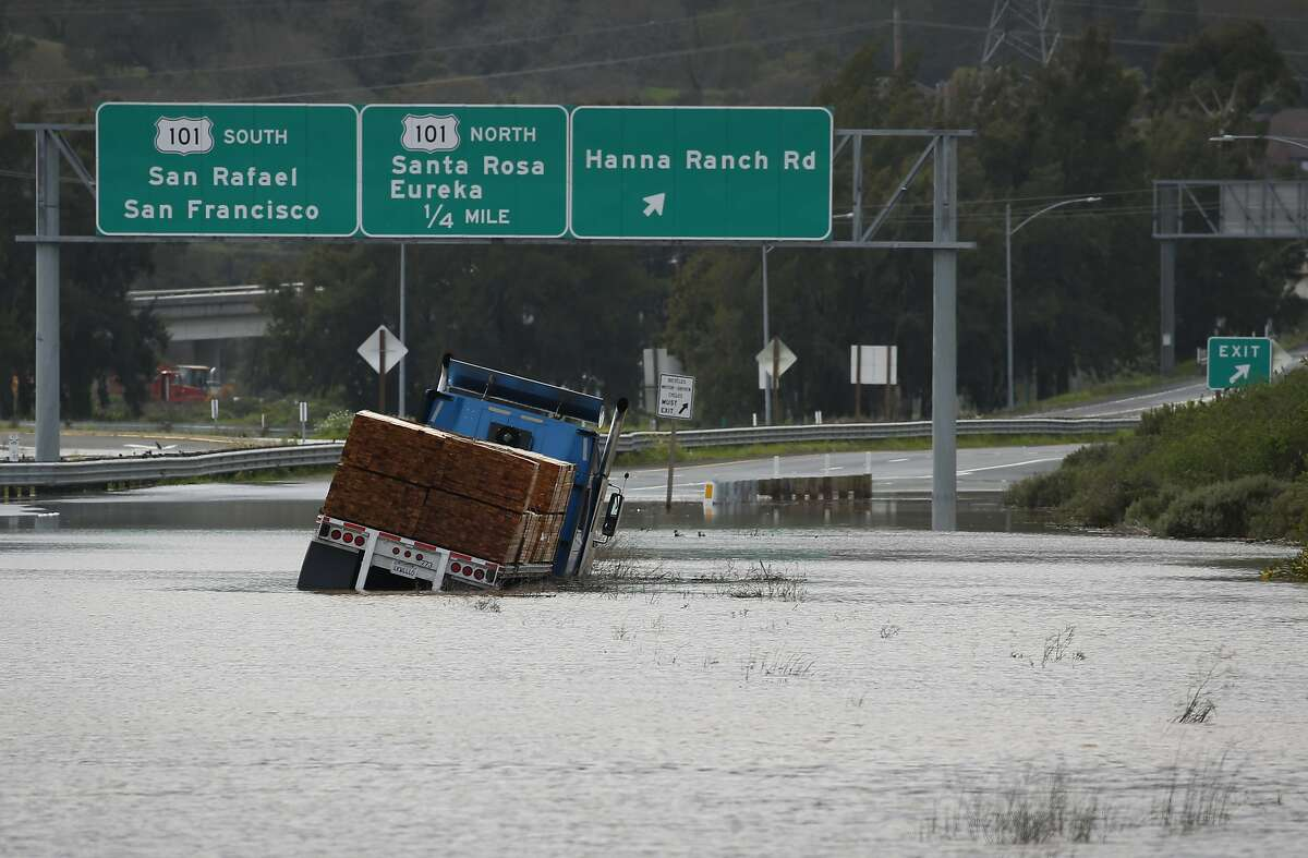 A big rig hauling lumber is trapped in flood water on westbound Highway 37 after water from heavy rainstorms flooded the roadway for the second time in a month closing the segment between Highway 101 and Atherton Avenue in Novato, Calif. on Wednesday, Feb. 27, 2019.