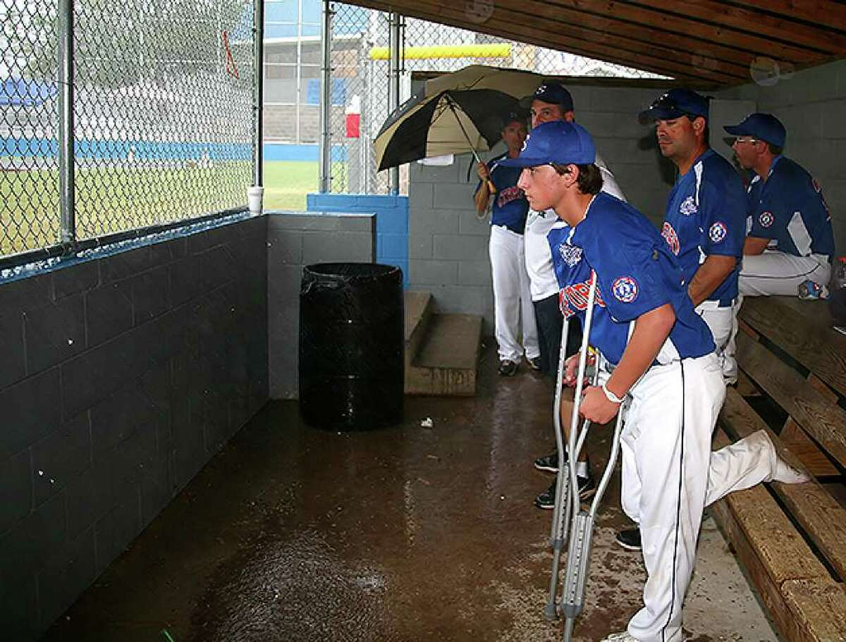 Stamford player Kyle Divico and the Stamford coaches watch from the dugout as rain falls on Burlington Field at the Babe Ruth World Series in Monticello, Arkansas on Sunday August 22, 2010. The game went into a rain delay.