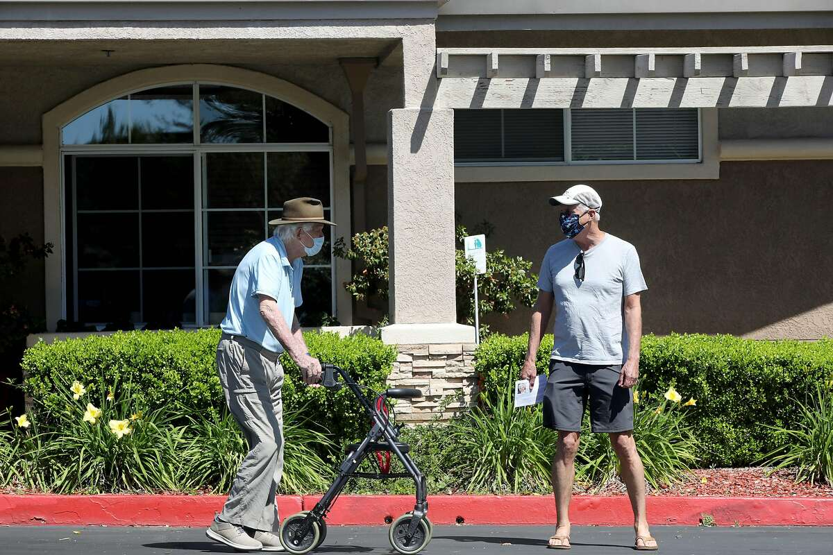 Jim Sander, 93, a resident at Carlton Senior Living, located at 175 Cleaveland Rd., listens to his son, Dave Sander, right, as they spend time together outside on Tuesday, May 5, 2020, in Pleasant Hill, Calif. The elder Sander has tested positive for COVID-19 at least twice. He has tested negative for the coronavirus from his last test.