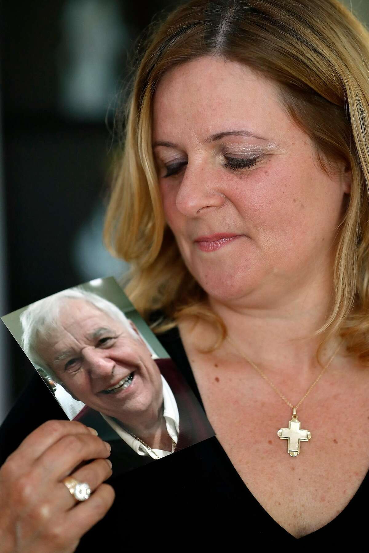 Tina Gullotta poses with a photo of her 87-year-old father, Harry Misthos in San Bruno, Calif., on Thursday, June 18, 2020. Misthos died from coronavirus earlier this year.