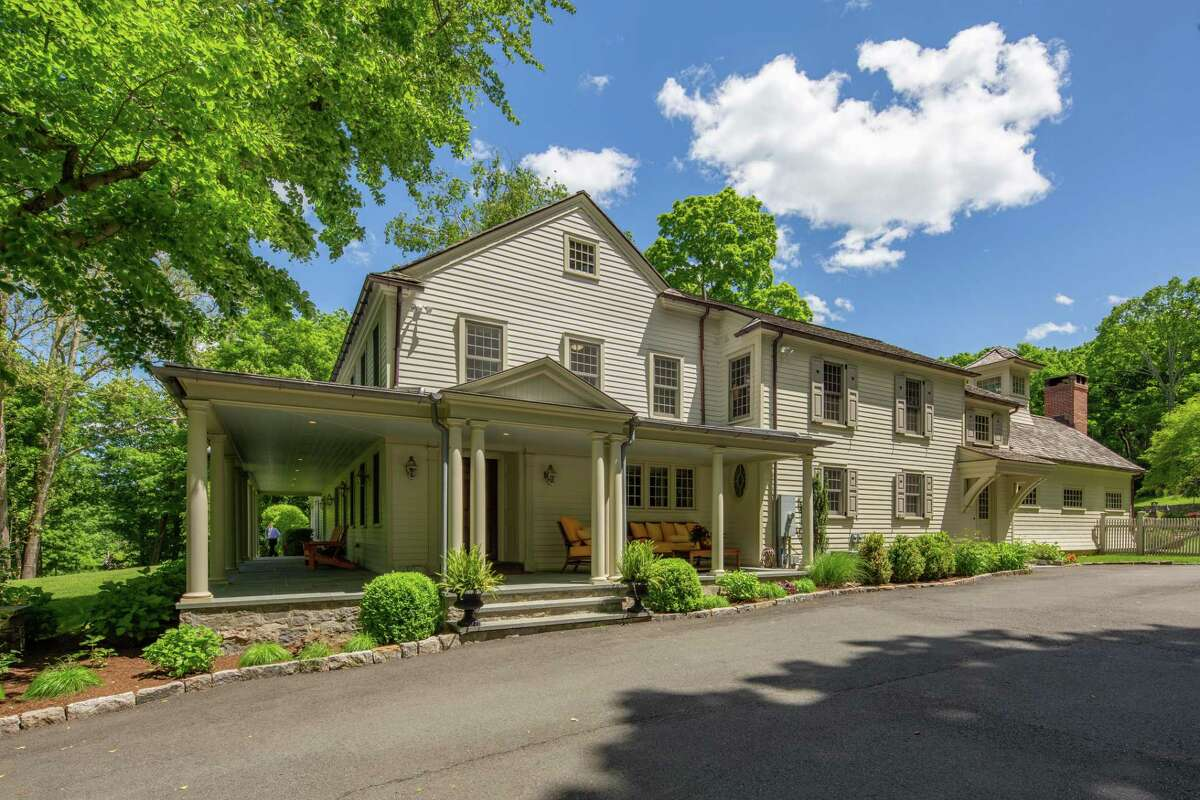 The stone, stucco, and clapboard colonial house at 67 Ridgefield Road sits on a corner lot only steps from Wilton Center.