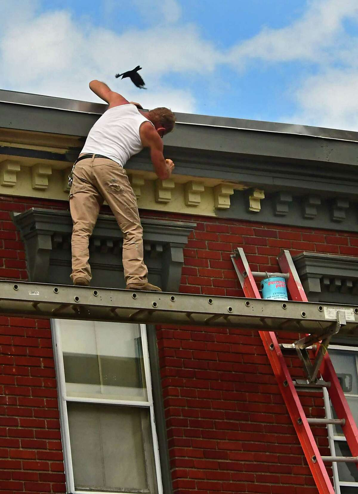 A man paints decorative molding on a building along Union Street on Wednesday, Aug. 5, 2020 in Schenectady, N.Y. (Lori Van Buren/Times Union)