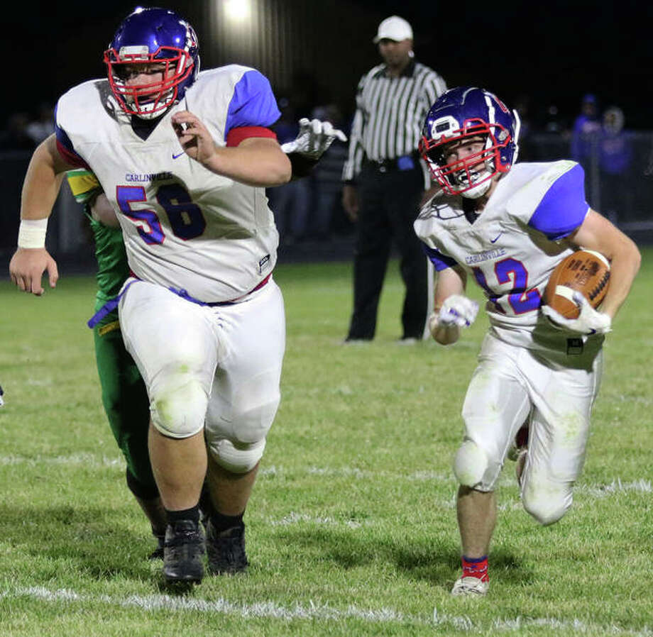 Carlinville offensive lineman Ethan Trimm (left) leads the way for running back Joe Lewis for a 38-yard run during a South Central Conference football game against Southwestern last season at Knapp Field in Piasa. Photo: Greg Shashack / The Telegraph
