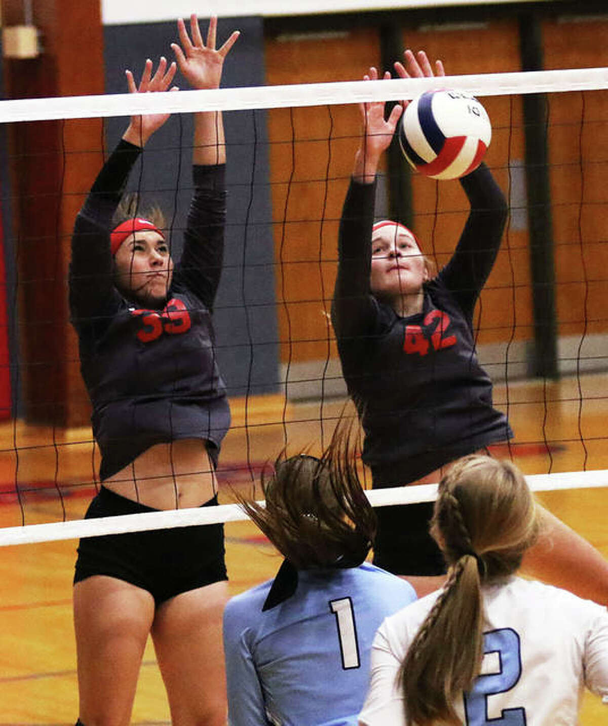 Staunton's Gabbie Reising (left) and Kennedy Legendre (42) go up for a double block to score against North Mac in a Macoupin County Tournament match last season in Carlinville. Both Reising and Legendre return from a 31-5 squad that will wait for spring for its next season.