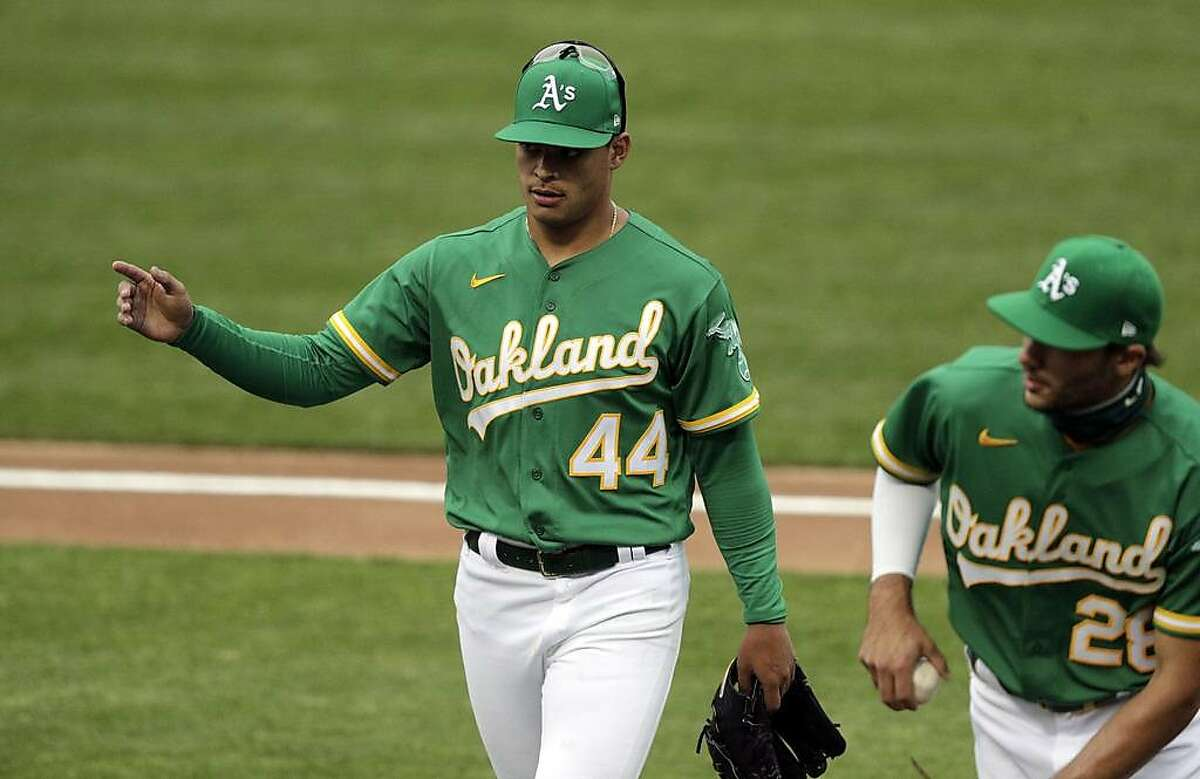 Jesus Luzardo (44) acknowledges teammates' applause as he walks off the field after the second inning as the Oakland Athletics played the Texas Rangers at the Coliseum in Oakland, Calif., on Tuesday, August 4, 2020.