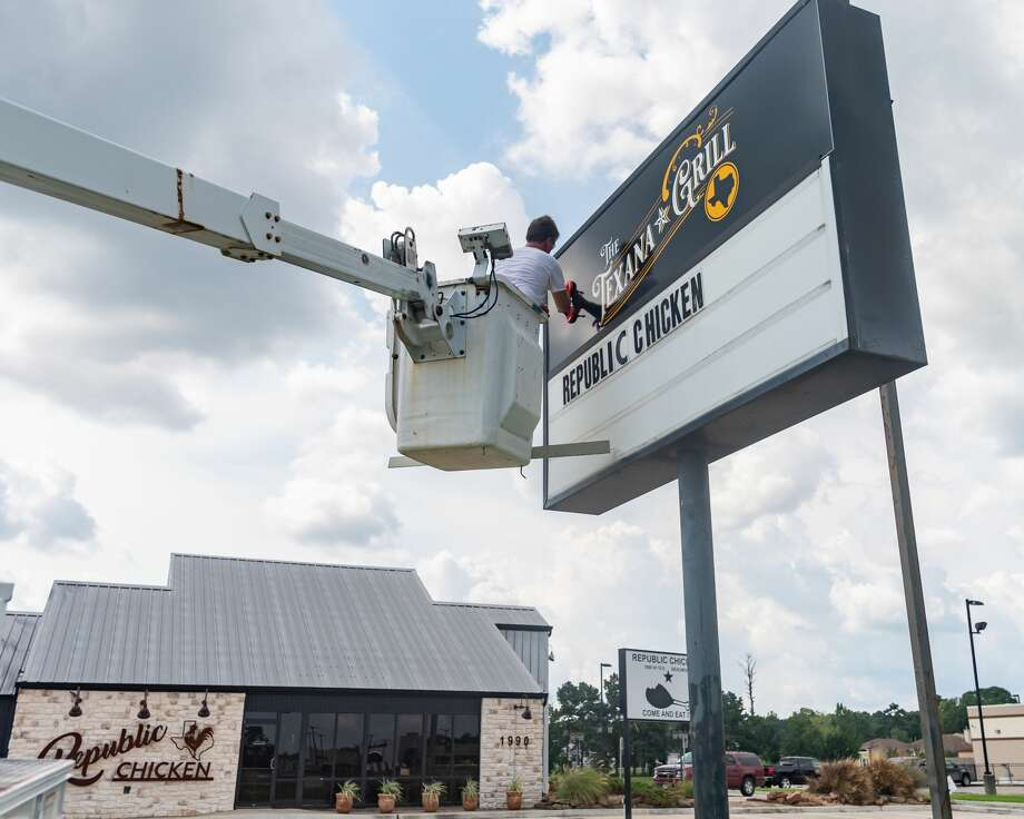 Cody Teems of Image 360 Beaumont installs the new sign for the former Republic Chicken. By next week, the eatery on Interstate 10 near Beaumont's hotel corridor will be transforming to The Texana Grill. Photo made on August 5, 2020. Fran Ruchalski/The Enterprise Photo: Fran Ruchalski/The Enterprise / © 2020 The Beaumont Enterprise